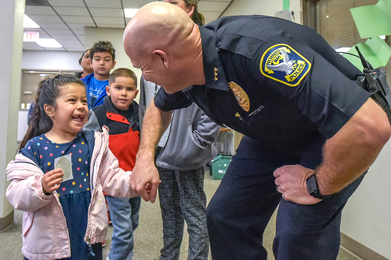 Southern Heights Pre-K student Giana Nila shakes Deputy Chief Brian Dunlap's hand